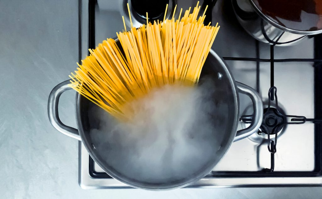 pot of pasta boiling on a stove with rising steam