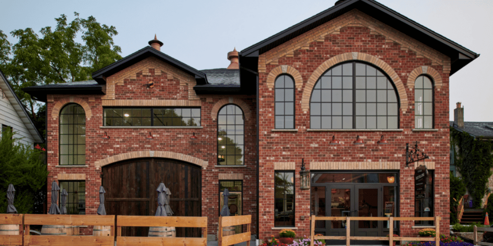 Black framed windows and doors on the Elora Distilling Company. Red brick building with black framed windows and doors looking from across the street.