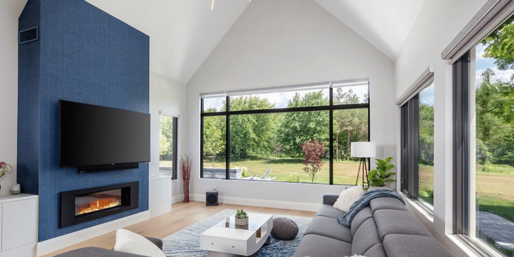 Living room with black window frames looking out to the backyard and a blue feature fireplace.